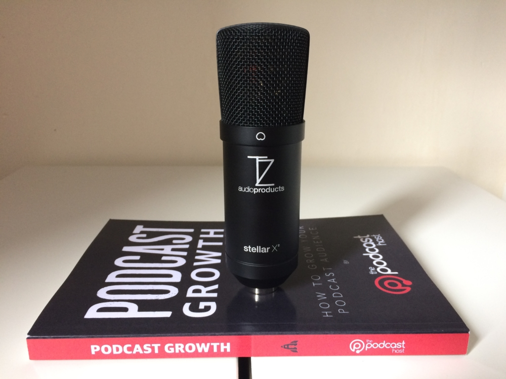 The mic poses with Podcast Growth book to give a size perspective